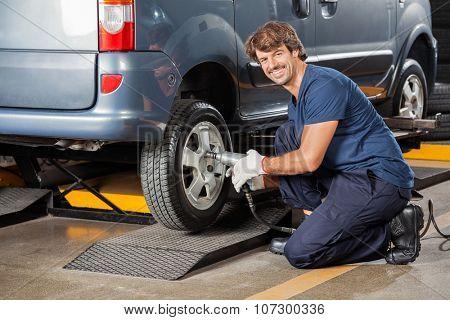 Side view of portrait confident male mechanic fixing car tire at auto repair shop