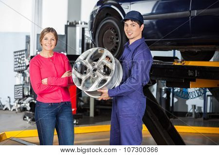 Portrait of confident mechanic holding hubcap with female customer at garage