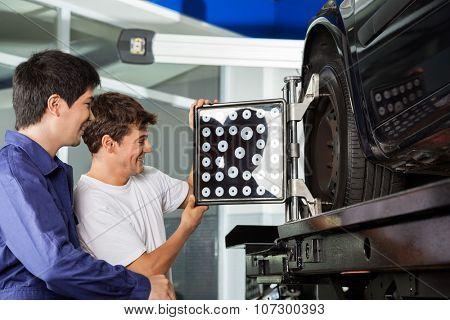 Smiling mechanics adjusting wheel aligner on car tire at garage