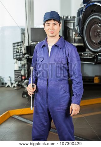 Portrait of confident male mechanic holding rim wrench while standing at garage