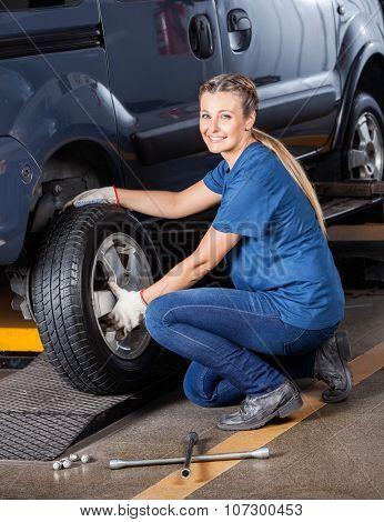 Portrait of confident female mechanic fixing car tire at auto repair shop
