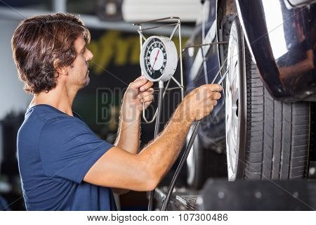 Side view of mechanic checking pressure while inflating car tire at garage