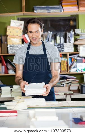 Portrait of confident mid adult male worker holding papers at workbench in factory