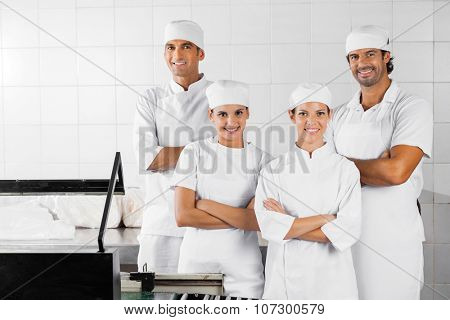 Portrait of confident male and female Baker's with arms crossed standing in bakery