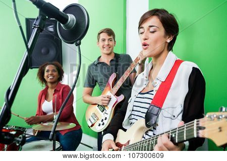 Young woman singing while band playing musical instrument in recording studio