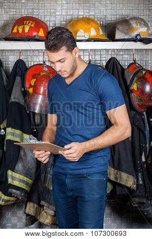 Firefighter reading clipboard against uniforms hanging at fire station