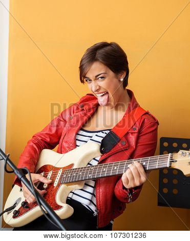 Portrait of joyful guitarist sticking out tongue while performing in recording studio