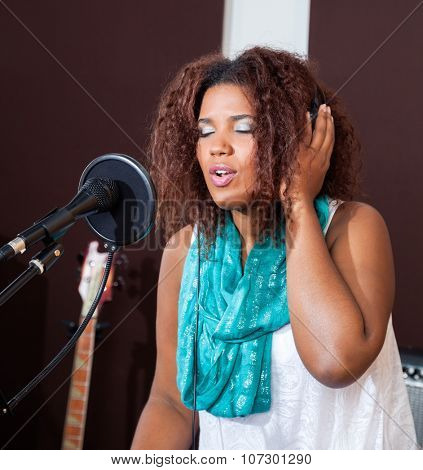 Young female singer with eyes closed performing in studio