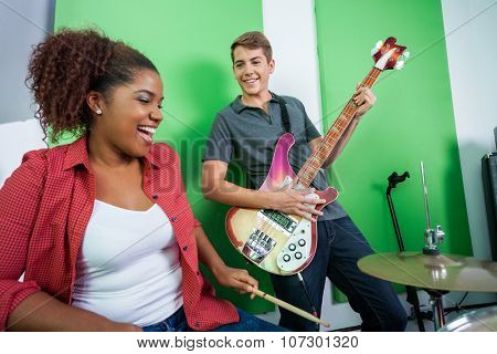 Happy male guitarist performing while looking at female drummer in recording studio