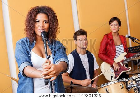 Portrait of female singer performing with band members in recording studio