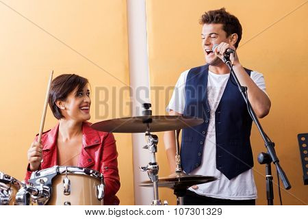 Happy male singer performing while looking at female drummer in recording studio