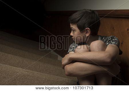 Sad Boy Sitting on Stairs