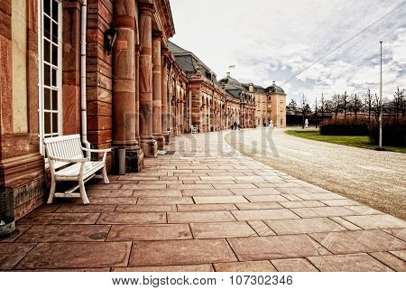 Red sandstone palace walkway with row of smooth columns.