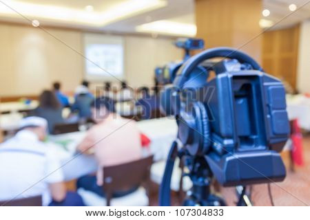 Blurred Photo Of Conference Meeting And Broadcasting Camera.
