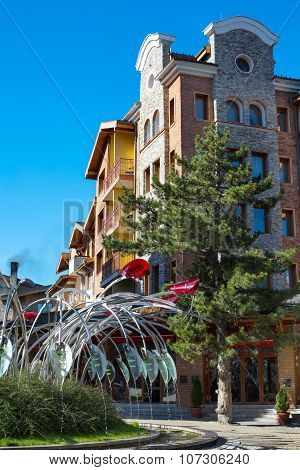 Downtown street view of Pirin Golf, nice houses, tree against blue sky