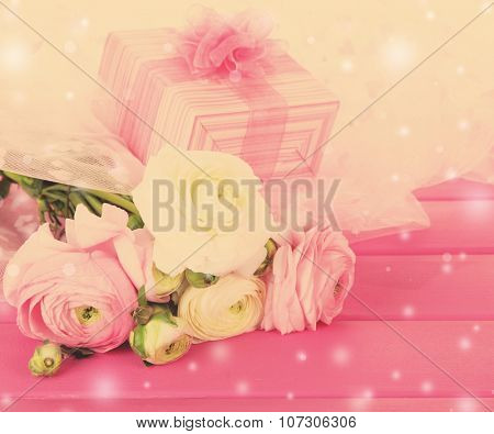 Ranunculus (persian buttercups) and gift box on wooden background