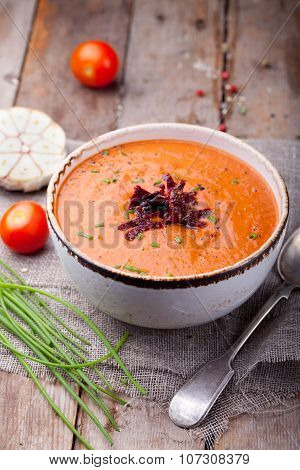 Tomato soup with sun dried tomatoes. Wooden background