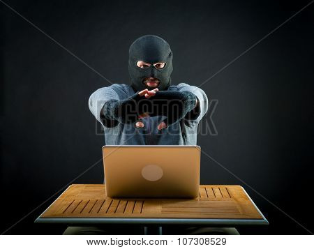 Hacker kneads hands before starting to crack the laptop