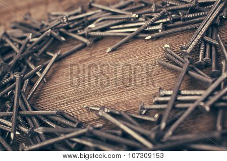 iron nails on wooden background