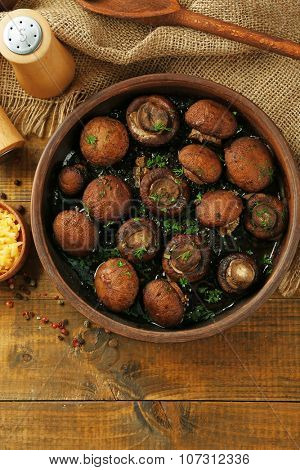 Baked champignons mushrooms with butter, parsley and roasted garlic in brown bowl
