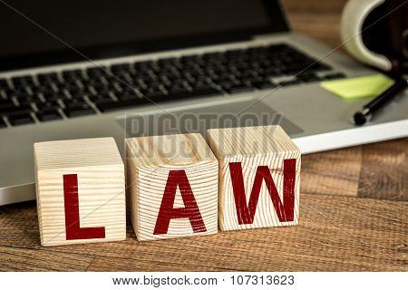 Law written on a wooden cube in a office desk