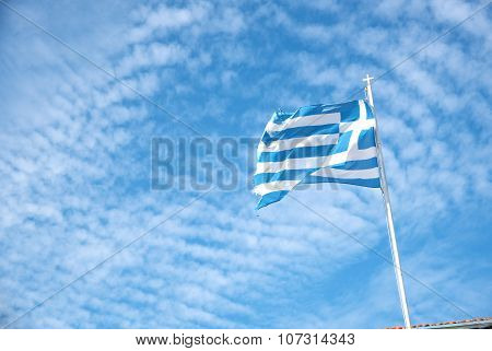 Greek Flag Waving Against A Blue Cloudy Sky
