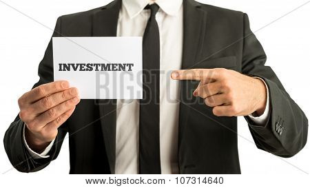 Financial Adviser Holding Up A White Card With Investment Sign