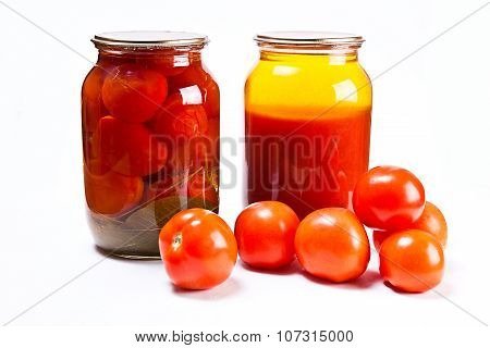Glass Jars Of Canned Tomatoes And Tomatoes Juice On White Background. Ripe Tomatoes In Front Of The