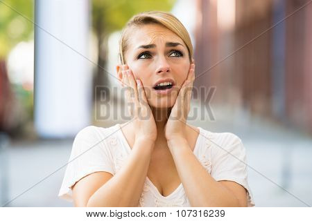Woman With Hands On Face Looking Up