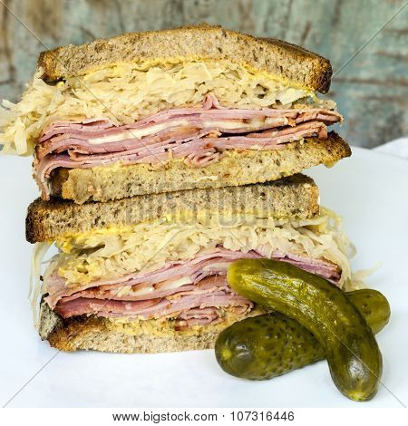 Reuben sandwich with dill pickle.  Corned beef, sauerkraut and cheese on sourdough.