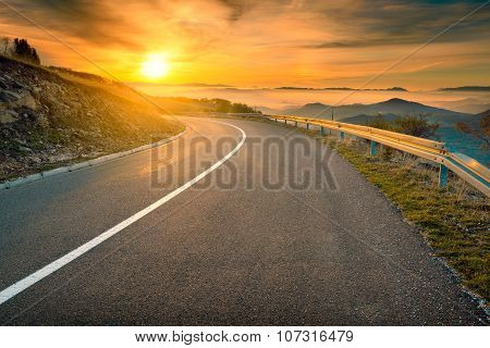 Driving On Mountain Road Against The Rising Sun