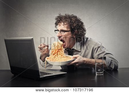 Man eating a huge dish of pasta in front of her laptop