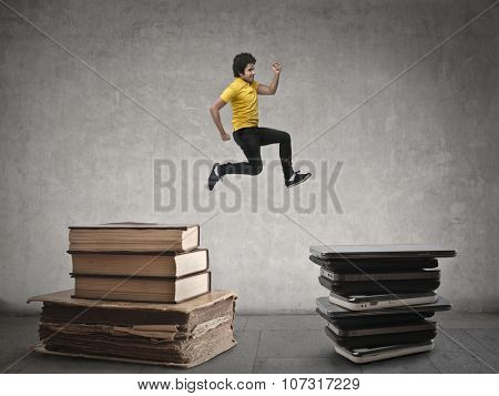 Man jumping from a pile of books to another