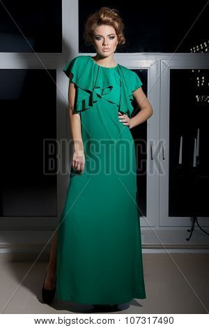 beautiful sexy elegant long-legged girl in a long green evening dress with evening hairstyle
