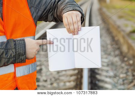 Railway Engineer with open empty book on railway