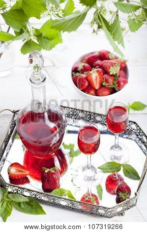 Strawberry and basil homemade liquor on a white background