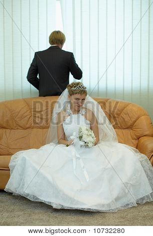 Braut sitzt auf der Couch, Bräutigam schaut aus Fenster