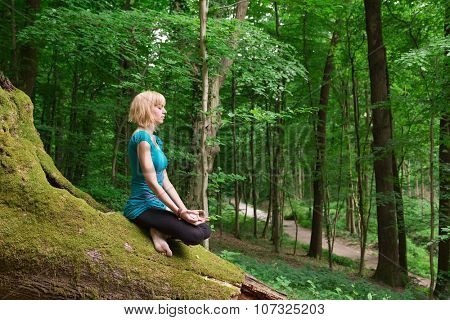 Young woman in seated meditation yoga pose in forest.