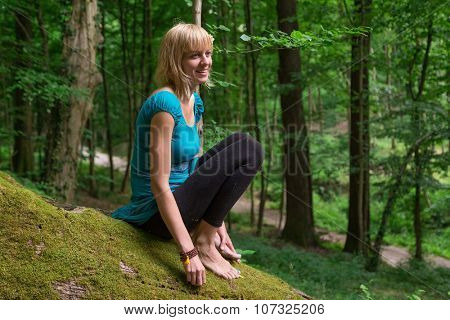Young woman practicing yoga in forest.