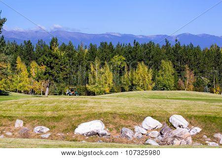 Pirin Golf Club panorama, golf cart,  green grass field, colorful trees, blue sky