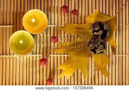 Lighted Candles with pine cones with yellow leaves on bamboo background