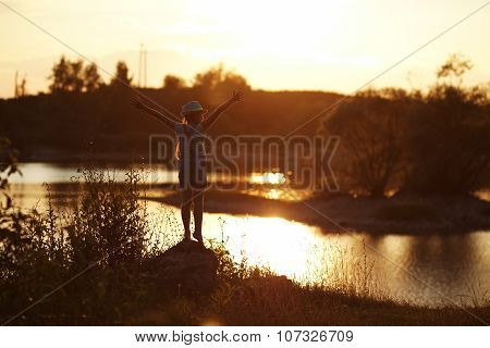 Girl Stands Near The River At Sunset