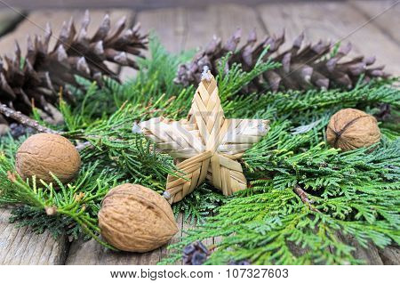 Christmas Star Made Of Straw On Green Pine Needles With Walnuts