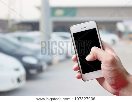 Mobile Hold In Hand With Blur Cars Parking