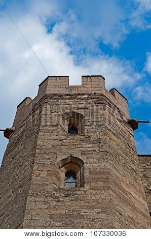 Exterior view of an antique medieval English castle tower facade from below