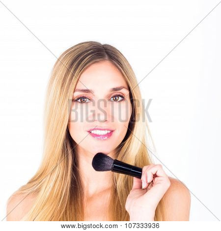 Happy smiling with teeth woman holding brush for rouge. Make-up close up.