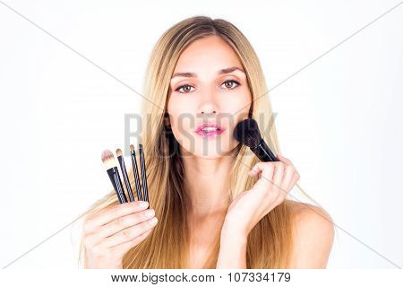 Young beautiful woman applying blush on the face. Make-up artist.