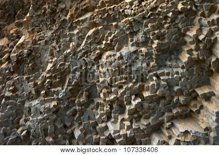The stunning geometrical pattern of stones on the rock, similar to the cubes, colored in gray, brown