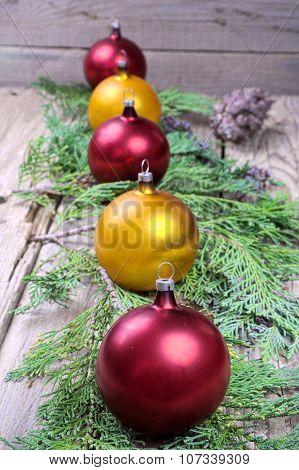 Five Colored Christmas Balls On Pine Needles On A Wooden Table