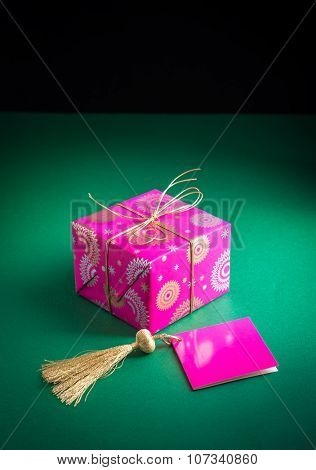 A small gift pack and an empty tag with golden tassel.